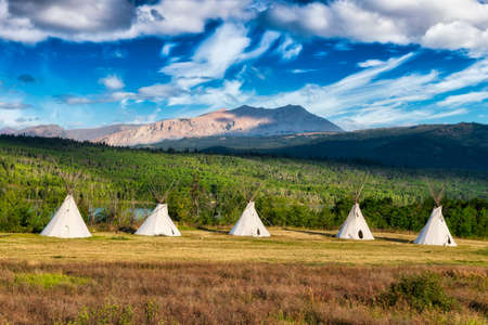 Beautiful View of the Tipi in a field with American Rocky Mountain Landscape in the background. Colorful Sunny Morning Sky. Taken in Montana near Glacier National Park, USA.