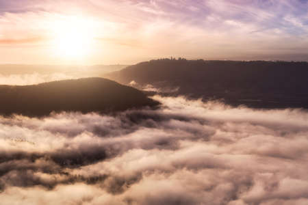 Dramatic Aerial View of cloud covered modern city and Burnaby Mountain. Colorful Sunrise Sky. Taken in Vancouver, British Columbia, Canada.