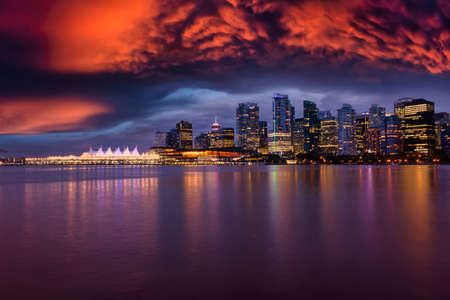 View of Coal Harbour in Downtown Vancouver, British Columbia, Canada, after Sunset. Modern City Skyline during Night. Dramatic Sky Artistic Render