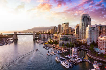 View of Burrard Bridge and False Creek in Downtown Vancouver, British Columbia, Canada. Taken during a beautiful cloudy sunset.