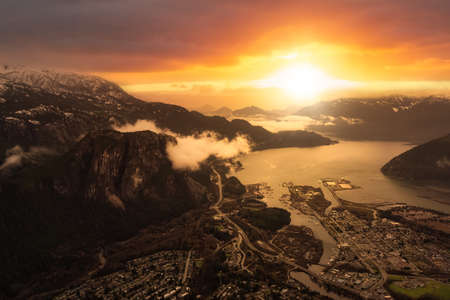 Aerial View of Chief Mountain, Sea to Sky Highway and Port in a Small touristic Town, Squamish. Located near of Vancouver, British Columbia, Canada. Dramatic Colorful Sunset Sky. 版權商用圖片