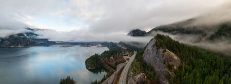 Aerial Panoramic view of Sea to Sky Highway with Chief Mountain in the background during a cloudy winter sunrise. Taken near Squamish, North of Vancouver, British Columbia, Canada.