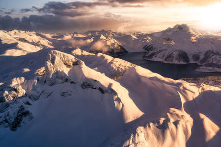 Beautiful aerial landscape view of snow covered mountain with a colorful sunset sky.