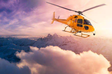 Yellow Helicopter flying over the Rocky Mountains during a sunny sunset. 版權商用圖片