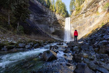 Girl watching a beautiful waterfall in Canadian Nature during winter. 版權商用圖片