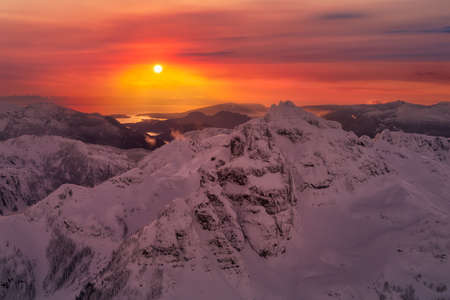 Aerial landscape view of the snow covered mountain range near Squamish and Vancouver, British Columbia, Canada. Artistic Sunset Sky Render