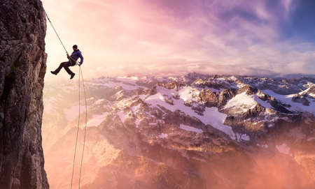 Epic Adventurous Extreme Sport Composite of Rock Climbing Man Rappelling from a Cliff. Mountain Landscape Background from British Columbia, Canada. Concept: Explore, Hike, Adventure, Lifestyle 版權商用圖片
