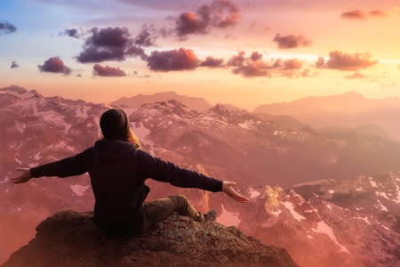 Adventurous Man with Open Hands is taking in the momen on top of a mountain. Fantasy Composite. Sunset or Sunrise Sky. Landscape from British Columbia, Canada. Фото со стока
