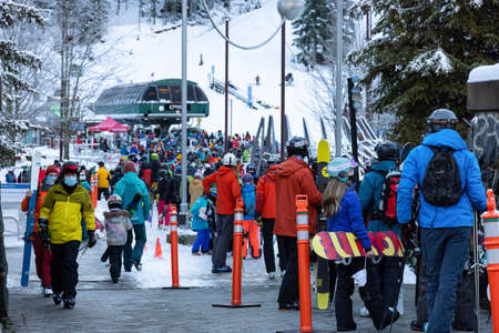 Whistler, British Columbia, Canada - December 28, 2020: Busy line up of people waiting for gondola to go ski and snowboard up the mountain during the Holiday Season.