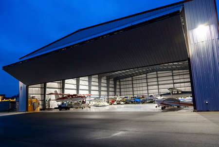 Pitt Meadows, British Columbia, Canada - December 28, 2020: Airplanes parked inside a hanger with a door open at an Airport.
