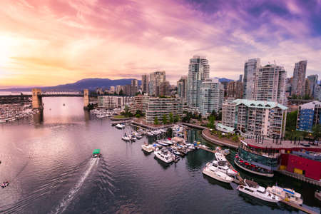 View of Burrard Bridge and False Creek in Downtown Vancouver, British Columbia, Canada. Modern City Architecture on the pacific west coast. Colorful sunset sky.