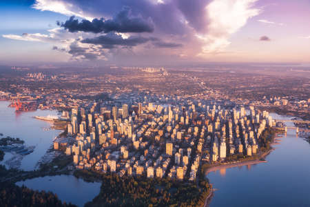 Aerial view of Stanley Park and Downtown Vancouver, BC, Canada. Dramatic Colorful Sunset Sky Art Render.