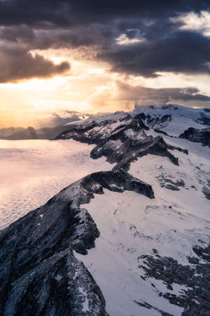 Beautiful aerial landscape view on the rocky mountains during a cloudy sunset. Taken near Vancouver and Squamish, British Columbia, Canada.