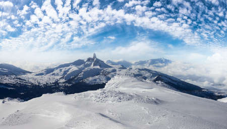 Beautiful Panoramic View of Black Tusk and Canadian Nature Landscape covered in Snow during winter. Blue Sky Art Render. Taken on top of Whistler Mountain, British Columbia, Canada. Nature Background