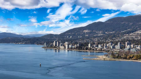 West Vancouver, British Columbia, Canada. Aerial Panoramic View of a modern cityscape on the Pacific Ocean Coast during a Winter sunny and cloudy evening.