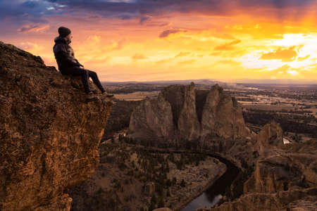 Man enjoying the Beautiful American Mountain Landscape. Dramatic Colorful Sunset Sky Art Render. Taken in Smith Rock, Redmond, Oregon, America. Concept: Adventure, Holiday and Travel