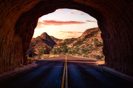 Middle of the road from tunnel view of a scenic route in American Canyons Mountain Landscape. Sunset Sky Art Render. Taken in Zion National Park, Utah, United States.