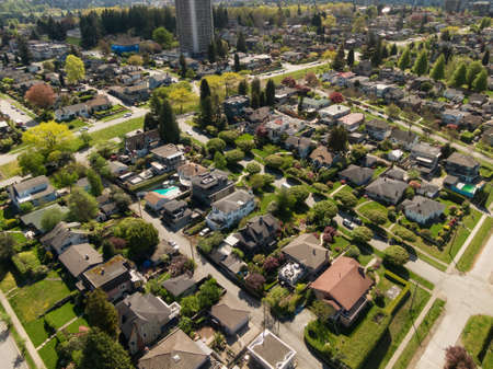 Aerial View from Above of Residential Homes in modern suburban city. Sunny Spring Day. Vancouver, British Columbia, Canada.