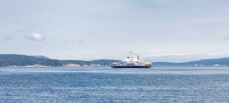 Victoria, Vancouver Island, British Columbia, Canada - August 18, 2021: BC Ferries Boat Arriving at the Terminal in Swartz Bay during sunny summer morning.