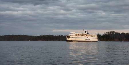 Victoria, Vancouver Island, British Columbia, Canada - August 21, 2021: BC Ferries Boat Leaving the Terminal in Swartz Bay during a cloudy summer sunset.