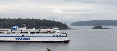 Victoria, Vancouver Island, British Columbia, Canada - August 21, 2021: BC Ferries Boat Arriving to the Terminal in Swartz Bay during a cloudy summer evening.