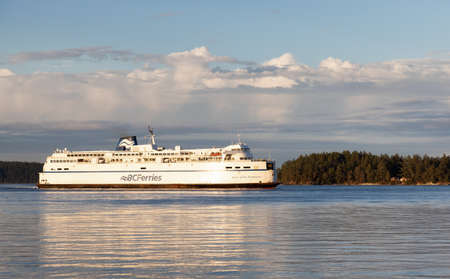 Victoria, Vancouver Island, British Columbia, Canada - August 26, 2021: BC Ferries Boat arriving at the Terminal in Swartz Bay during cloudy summer sunset.