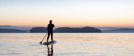 Adventurous Caucasian Adult Woman on a Stand Up Paddle Board is paddling on the West Coast of Pacific Ocean. Sunny Sunrise. Victoria, Vancouver Island, BC, Canada. Standard-Bild