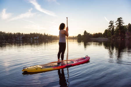Adventurous Caucasian Adult Woman Paddling on a Stand up Paddle Board in water at a city park. Sunny Sunset Sky. Gorge Park, Victoria, Vancouver Island, BC, Canada.