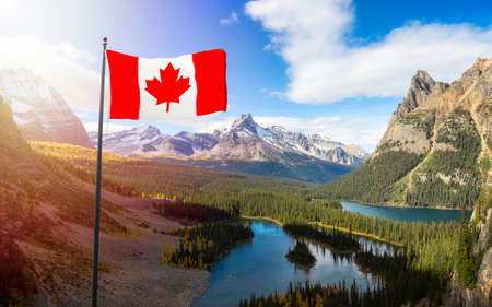 Canadian National Flag Composite with Canadian Rocky Mountains in Background. Sunny Fall Day. Located in Lake OHara, Yoho National Park, British Columbia, Canada.