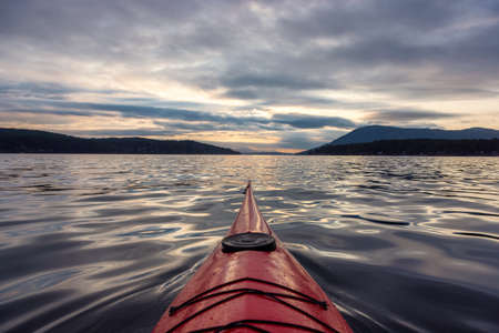 Sea Kayak paddling in the Pacific Ocean. Dramatic Sunset Sky. Taken near Victoria, Vancouver Islands, British Columbia, Canada. Concept: Sport, Adventure