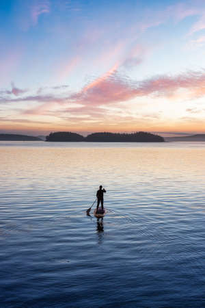 Adventurous Caucasian Adult Woman on a Stand Up Paddle Board is paddling on the West Coast of Pacific Ocean. Sunny Sunrise Sky Art Render. Victoria, Vancouver Island, BC, Canada. Standard-Bild