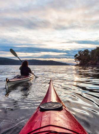Adventurous Woman on Sea Kayak paddling in the Pacific Ocean. Summer Sunset Sky. Taken near Victoria, Vancouver Islands, British Columbia, Canada. Concept: Sport, Adventure