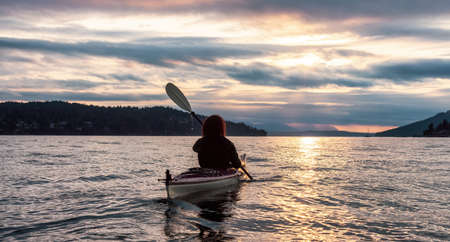 Adventurous Woman on Sea Kayak paddling in the Pacific Ocean. Summer Sunset Sky. Taken near Victoria, Vancouver Islands, BC, Canada. Concept: Sport, Adventure