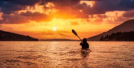 Adventurous Woman on Sea Kayak paddling in the Pacific Ocean. Dramatic Sunset Sky Art Render. Taken near Victoria, Vancouver Islands, British Columbia, Canada. Concept: Sport, Adventure