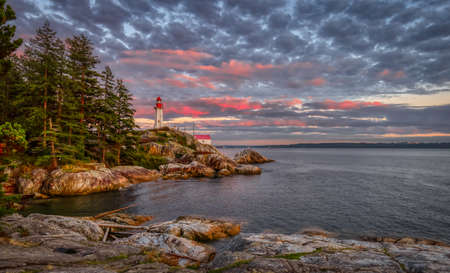 Lighthouse Park on a rocky coast during a dramatic cloudy sunset. Horseshoe Bay, West Vancouver, British Columbia, Canada. Nature Background