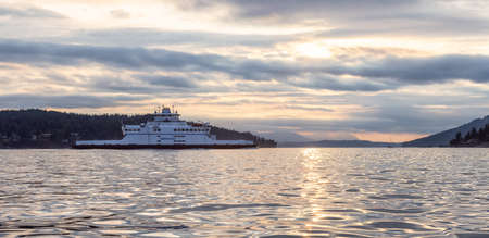 Victoria, Vancouver Island, British Columbia, Canada - August 20, 2021: BC Ferries Boat Arriving to the Terminal in Swartz Bay during cloudy summer sunset.