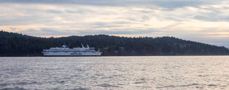 Victoria, Vancouver Island, British Columbia, Canada - August 20, 2021: BC Ferries Boat leaving the Terminal in Swartz Bay during cloudy summer sunset.