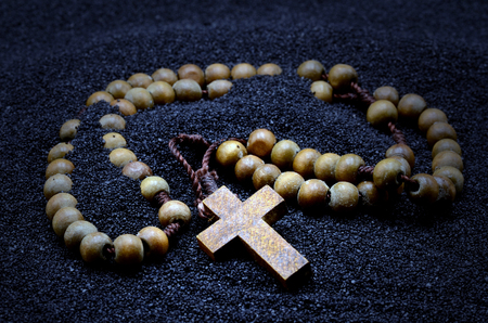 Rosary in a black sand close up photo Banco de Imagens - 83006330