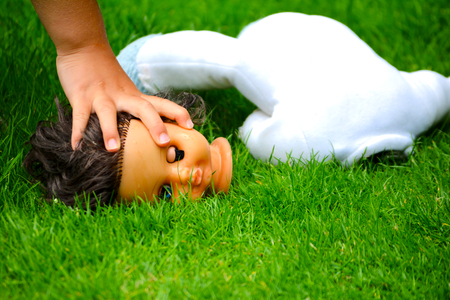 Doll head and child in a green grass photo