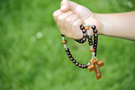 religious clothing: Rosary in child hands close up photo