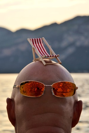 little small beachchair on a bald head with sunglases