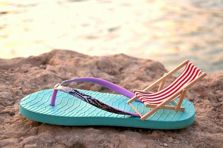 Flipflop mit Strandkorb auf einem Stein hautnah hinter dem Meer