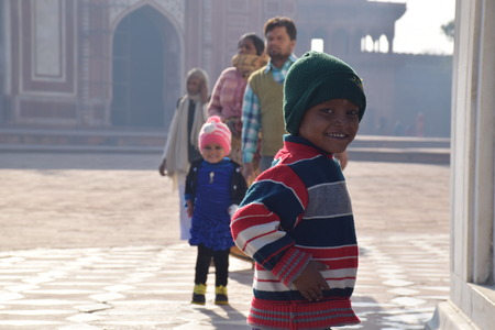 love dome: Indian kid with hat smiling in front of the room inside the Taj Mahal, Agra, Uttar Pradesh, India Editorial