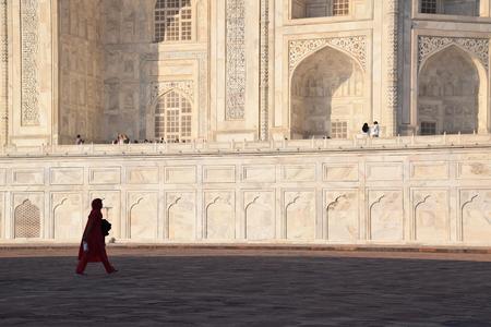 love dome: Indian woman dressed in red walking inside the Taj Mahal, Agra, Uttar Pradesh, India