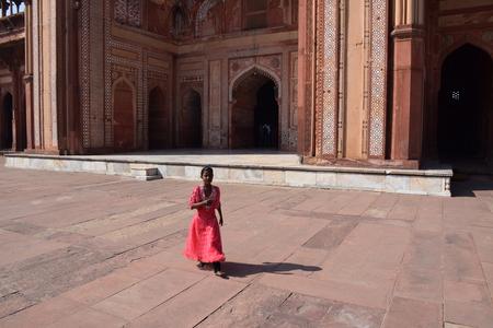 uttar pradesh: Little indian girl walking in the old mosque of Fatehpur Sikri, Uttar Pradesh, India Editorial
