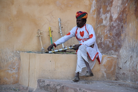 amber fort: Indian man with traditional musical instrument outside Amber Fort in Jaipur, Rajasthan, India