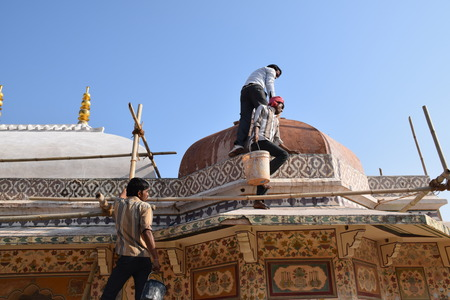 amber fort: Indian men working without any safety devices on a roof of Amber fort in Jaipur, Rajasthan, India Editorial