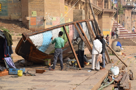uttar pradesh: Indian people repairing a wooden boat on the ghats of Varanasi, Uttar Pradesh, India
