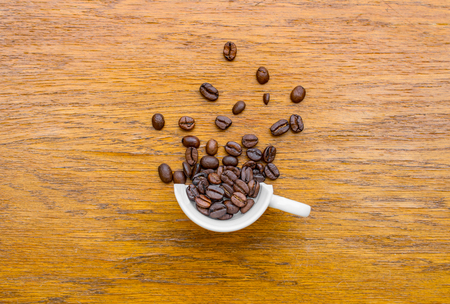 Flat view of a half cup of coffee and coffee beans on a wooden surface with warm colors. Impression of coffee splashing out of it