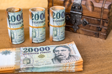 Stack of Hungarian money and rolled up 20000 banknotes with a closed vintage wooden box in the background Stock Photo